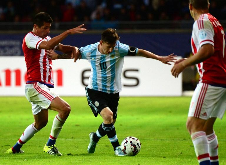 Argentina's forward Lionel Messi and Paraguay's midfielder Victor Caceres vie for the ball during their 2015 Copa America football championship match, in La Serena, on June 13, 2015.  AFP PHOTO / MARTIN BERNETTI