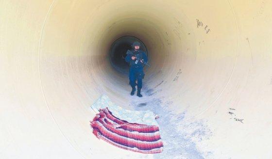 """Un policía recorre el túnel que habría sido usado por el """"Chapo"""" Guzmán"""