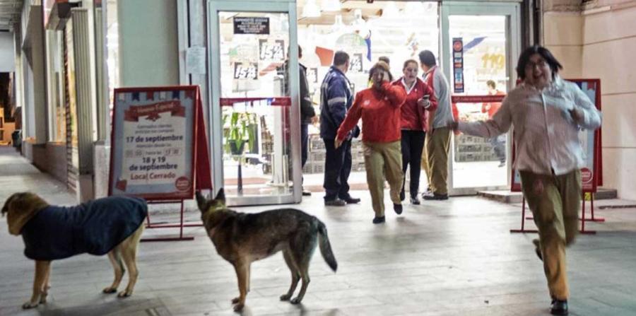 Varias personas salen corriendo de un supermercado en Santiago tras el fuerte terremoto que se registró esta noche en Chile