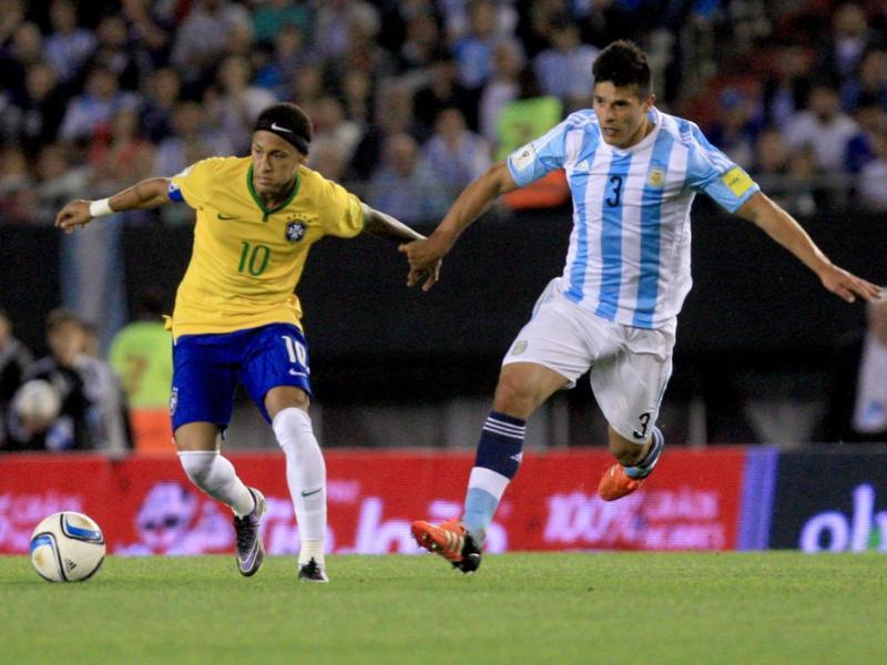 El jugador Facundo Roncaglia, de Argentina, disputa el balón con Neymar, de Brasil.