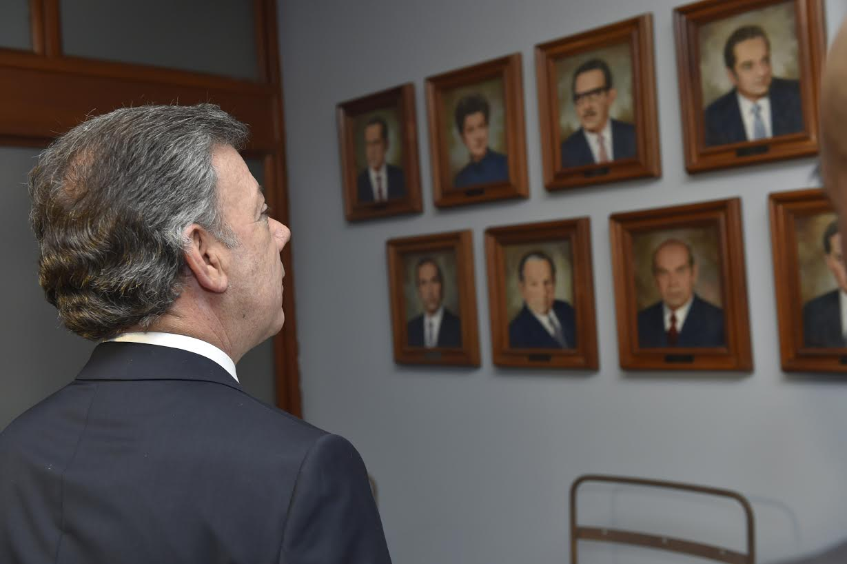 Juan Manuel Santos Calderón, observa las imágenes de los magistrados de la Corte Suprema de Justica inmolados el 6 y el 7 de noviembre de 1985 en Bogotá.