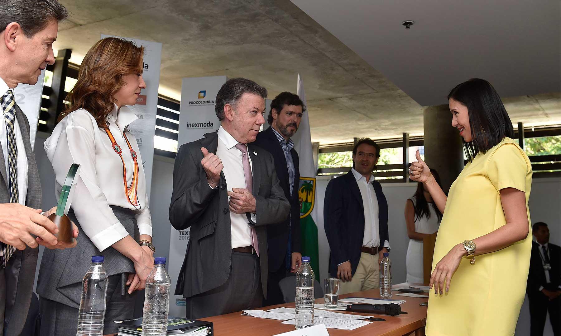 El Presidente Santos le muestra la marca de su vestido 'Arturo Calle' a Natalia Díaz, directora regional comercial de esta empresa comercializadora de ropa masculina, reconocida durante la feria de Colombiamoda, que se realiza en Medellín.