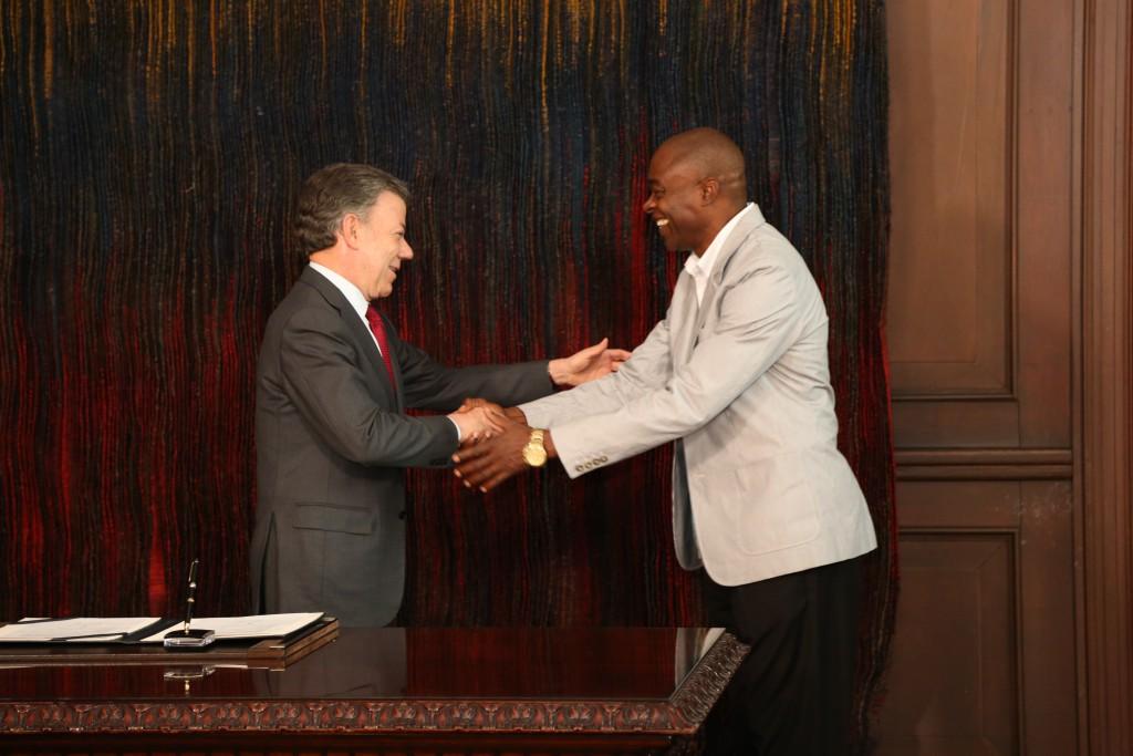 El Presidente Juan Manuel Santos saluda a Ubaldo Duany, técnico de Caterine Ibargüen, luego de otorgarle la nacionalidad colombiana.