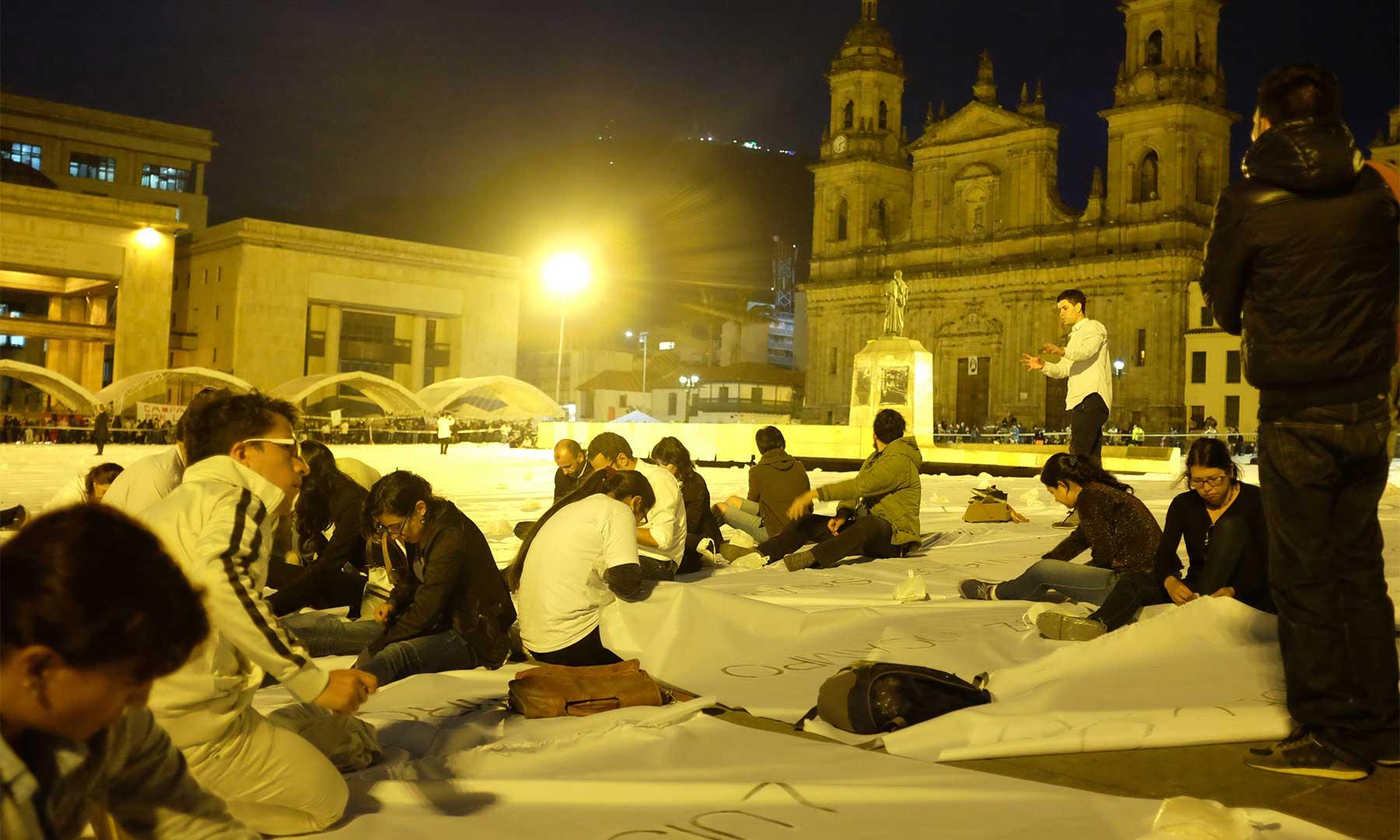 """En la Plaza de Bolívar, miles de jóvenes cosen una gigantesca bandera, de la obra denominada """"Sumando ausencias"""" de la artista Doris Salcedo, que se constituye en una acción de paz en memoria de las víctimas del conflicto."""