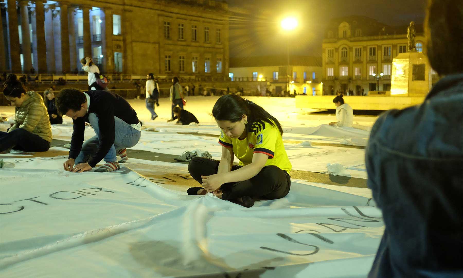 """Más de 3.500 colombianos se reunieron en la Plaza de Bolívar para coser las secciones de una gigantesca bandera blanca, una obra de la artista Doris Salcedo denominada """"Sumando ausencias""""."""