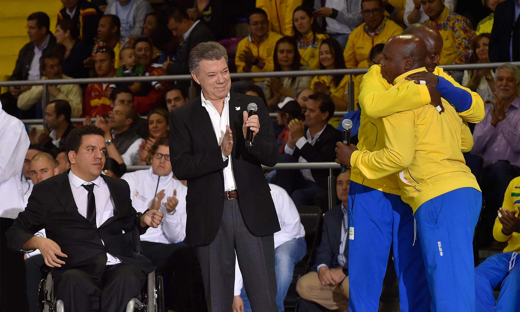Dos jugadores ruandeses de voleibol sentado y que antes fueron combatientes de bandos distintos en el conflicto de su país, dan una muestra de reconciliación con un abrazo, en presencia del Presidente Santos.