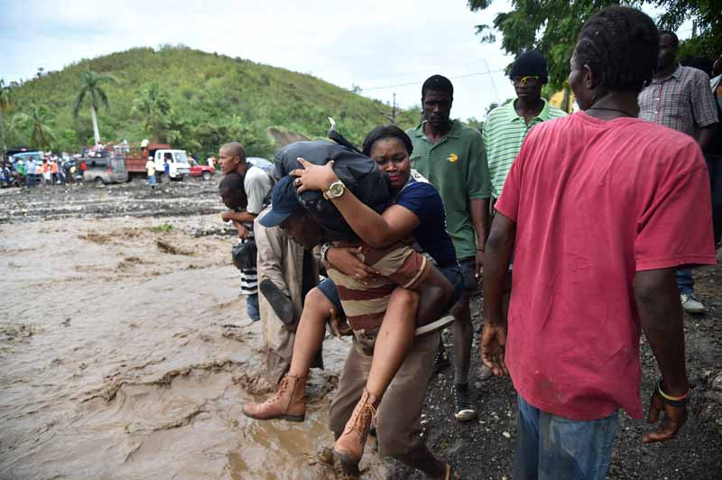 Haitian people cross the river La Digue in Petit Goave where the brid
