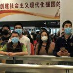Noticias ONU/Jing Zhang Gente con mascarillas espera en la zona de llegadas del aeropuerto internacional de Shenzhen Bao'an