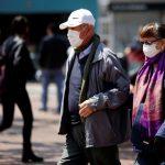 Personas adultas caminan usando tapabocas como medida preventiva para evitar el contagio del coronavirus en una calle de Bogotá