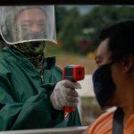 Un oficial de policía verifica la temperatura corporal de un pasajero en un punto de control de cuarentena en medio del estricto bloqueo reimpuesto para frenar las infecciones por COVID-19, en la ciudad de Quezon, Metro Manila, Filipinas,  REUTERS / Eloisa Lopez