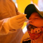 Un miembro de un equipo médico toma una muestra a una niña para detectar  COVID-19 en una de las zonas con más infecciones en Bogotá,  REUTERS/Luisa González