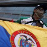Un hombre utilizando una mascarilla sostiene una bandera en medio de manifestaciones en Bogotá, Colombia. Septiembre 7, 2020. REUTERS/Luisa Gonzalez