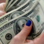 Una mujer cuenta billetes de cien dólares estadounidenses, en Buenos Aires, Argentina. REUTERS/Marcos Brindicci