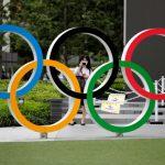 Una mujer utilizando mascarilla toma una fotografía a os anillos olímpicos frente al Estadio Nacional de Tokio, Japón REUTERS/Kim Kyung-Hoon