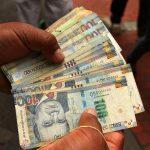 Un trabajador de una casa de cambio sostiene billetes de soles peruanos en Lima, Perú. REUTERS/Mariana Bazo