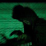 Un hombre encapuchado sostiene un computador portátil mientras se proyecta un código cibernético sobre él en esta foto de ilustración tomada el 13 de mayo de 2017. El principal operador de oleoductos de combustible de Estados Unidos, Colonial Pipeline, ha cerrado toda su red tras un ciberataque, según ha informado la compañía este viernes. REUTERS/Kacper Pempel/Ilustración