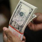 Un paquete de billetes de cinco dólares es inspeccionado en la Oficina de Grabado e Impresión de Washington. REUTERS/Gary Cameron/File Photo