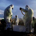 Sepultureros con equipo de protección personal (EPP) entierran el ataúd de una víctima de la enfermedad por coronavirus (COVID-19), en el área de entierro proporcionada por el gobierno para las víctimas del COVID-19, en Yakarta, Indonesia, 28 junio 2021. REUTERS/Willy Kurniawan
