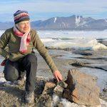 La empresaria suiza Christiane Leister, creadora de la Fundación Leister que financió la expedición que descubrió una pequeña isla frente a la costa de Groenlandia y que afirman es el segmento de tierra más septentrional del mundo, frente a un canto en el que miembros de su expedición dejaron un mensaje con detalles de su visita. Julian Charriere/via REUTERS